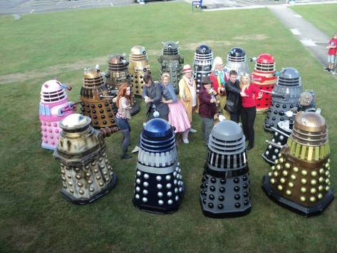 4th Doctor: Nicki Martyn 5th Doctor: Rich Walters 6th Doctor: Chris Kingbees 9th Doctor: Jon-Michael Lindsey 10th Doctor: Richard Ashton Rose (S1): Liz Adnitt Rose (50's): Naomi Gibbs Amy Pond: Bex Hemington  The Daleks surround the Doctors and Companions...  Photo from: Dalek Candi